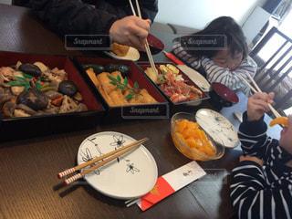 食品のプレートをテーブルに座っている女性の写真・画像素材[975251]