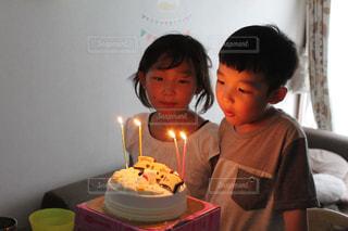 キャンドルとバースデー ケーキの前に立っている少年の写真・画像素材[1683341]