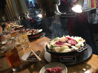 食品のプレートをテーブルに座っている女性の写真・画像素材[912503]