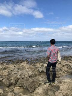 岩のビーチに立っている人 - No.1013210