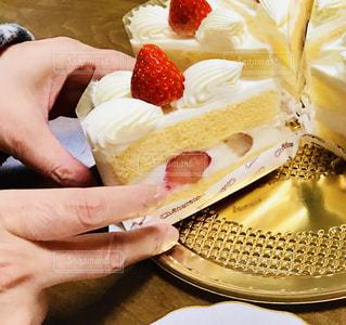 テーブルの上のケーキを持っている手の写真・画像素材[895788]