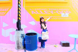 ピンクのオシャレな壁の前でポーズする女の子 - No.866721