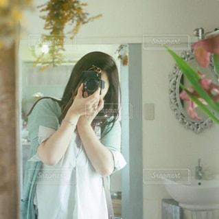 カメラにポーズ鏡の前に立っている女性の写真・画像素材[1831056]