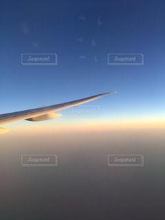 青い空を飛ぶ大型旅客機の写真・画像素材[1100174]