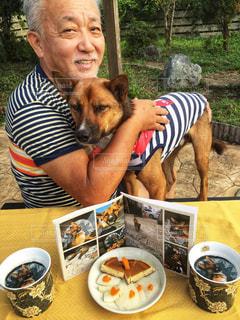 犬と一緒にテーブルに座って人の写真・画像素材[1460538]