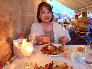 食物と一緒にテーブルに座っている女性の写真・画像素材[1640462]