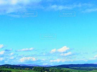 空の雲と大規模なグリーン フィールドの写真・画像素材[1867781]