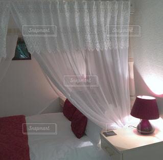 ベッドとカーテンのあるベッドルームの写真・画像素材[2179229]