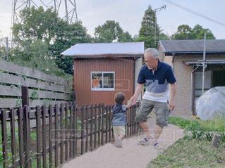 フェンスの隣に立っている少年の写真・画像素材[2267540]