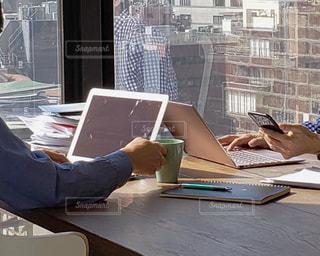 ラップトップコンピュータを使ってテーブルに座っている人の写真・画像素材[2310936]