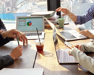 ラップトップコンピュータを使ってテーブルに座っている人の写真・画像素材[2330561]