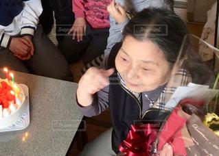 誕生日ケーキを食べにテーブルに座っている人々のグループの写真・画像素材[2831220]