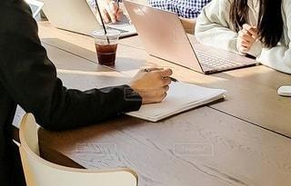 ラップトップコンピュータを使ってテーブルに座っている人の写真・画像素材[3302230]