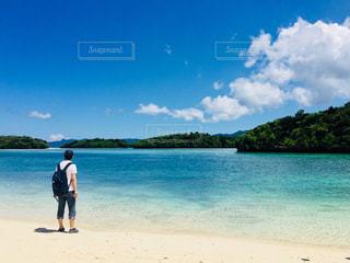水の体の近くのビーチに立っている人の写真・画像素材[925129]