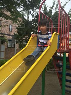 スライド上に座っている若い男の子の写真・画像素材[908452]