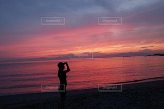 夕焼けを背景にビーチで凧を飛ばす人の写真・画像素材[2378921]