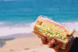 サンドイッチを持っている手の写真・画像素材[1158949]