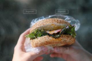 半分を握っている手がサンドイッチを食べ - No.1197291