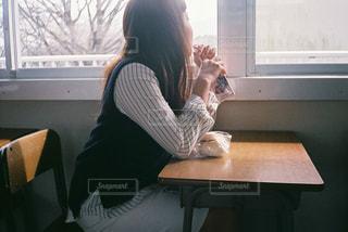 窓の前のテーブルに座っている人の写真・画像素材[1232978]