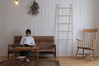 部屋の椅子に座っている人の写真・画像素材[2928556]