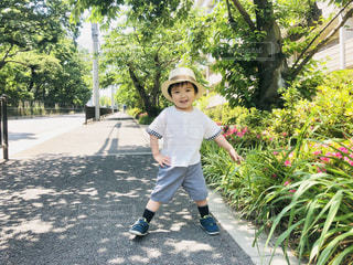 木の隣に立っている少年の写真・画像素材[2293273]