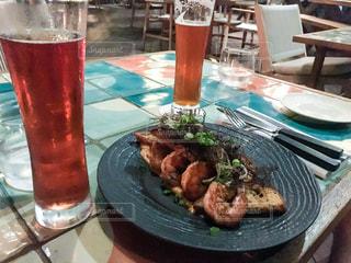 食べ物やビール、テーブルの上のガラスのプレート - No.911083