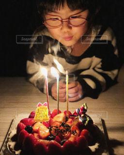 バースデー ケーキでテーブルに座っている人の写真・画像素材[1693011]
