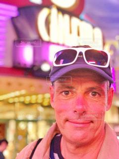 帽子とサングラスのカメラにポーズを身に着けている男の写真・画像素材[1032149]