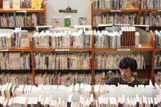本でいっぱいの本棚の前に立っている人の写真・画像素材[2492099]