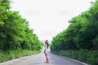 未舗装の道路を歩いて女性の写真・画像素材[929189]