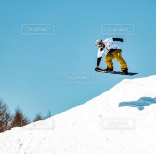 雪に覆われた丘を下ってスノーボードに乗っている間空気を通って飛んで男 - No.931889