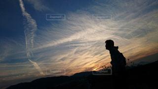 バック グラウンドで夕日を持つ人の写真・画像素材[986787]