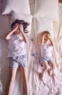 ベッドの上で横になっているドレスを着た女の子の写真・画像素材[1621565]