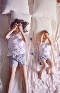 ベッドの上で横になっているドレスを着た女の子の写真・画像素材[1621590]