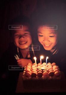 キャンドルとバースデー ケーキの前で小さな女の子の写真・画像素材[1621603]