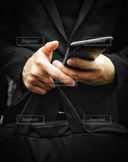 スマホをいじるビジネスマンの写真・画像素材[1642822]