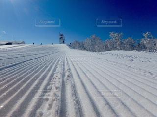 雪に覆われた斜面をスキーに乗る男 - No.933489