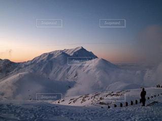 雪に覆われた山に立つ男の写真・画像素材[1017391]