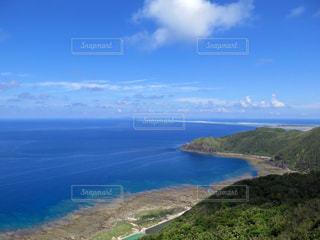 近くに水の体の横にある丘の中腹のアップの写真・画像素材[1201125]