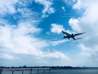 曇りの青い空を飛んでいるジェット大型旅客機の写真・画像素材[908415]