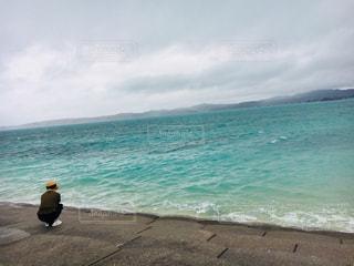海の横にあるビーチの上を歩く男の写真・画像素材[908425]