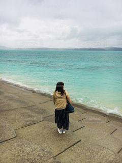 ビーチに立っている女性の写真・画像素材[908428]