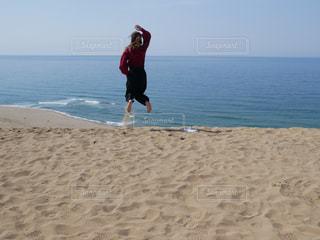 浜辺で空中を飛んでいる男の写真・画像素材[2140952]
