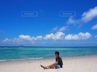 沖縄の海・瀬底ビーチに座る男性 - No.898519