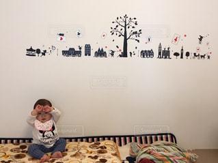 ベッドの上に座っている小さな子供の写真・画像素材[1006667]