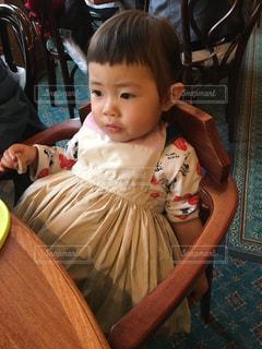 テーブルに座っている小さな子供の写真・画像素材[1027397]