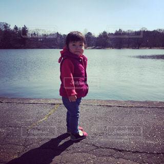 湖の前で立っている娘の写真・画像素材[1100976]