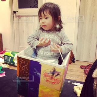 小さな女の子のテーブルに座っての写真・画像素材[1213858]
