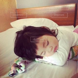 ベッドの上で横になっている少女の写真・画像素材[1262160]