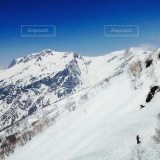 雪覆われた山の中腹に立っている人々 のグループの写真・画像素材[1393797]